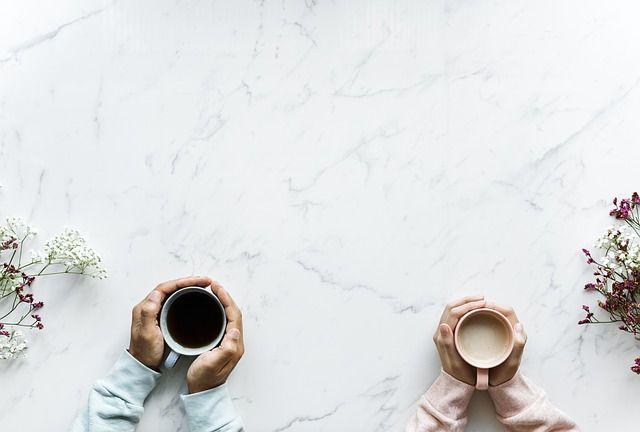 Dos tazas de café desde arriba sujetas por manos